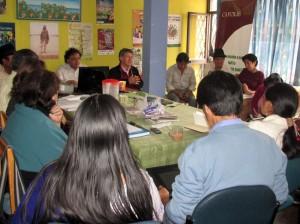 Fernando Rosero (chompa negra, gesticulando) en reunión de mesas comunitarias.